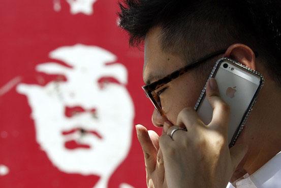 Reuters: Mann in Peking mit iPhone. Apple wird auch China Mobile mit der günstigeren Variante des iPhones beliefern